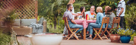 Group of friends eating grilled food during meeting in the yard Stock Photo