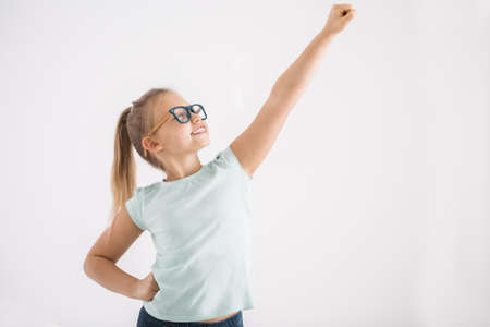 Portrait of a young girl with her arm and fist up and the other arm on a hip in a superhero pose on white wall background