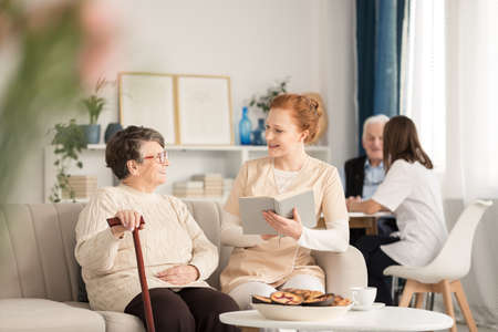 Professional caretaker in uniform reading a book to a happy senior woman with cane while sitting on a couch during leisure time in luxury nursing home common room with other people by a table in the background Reklamní fotografie