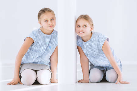 Portrait of young, happy twin sisters kneeling and leaning against opposite sides of a white wall Standard-Bild