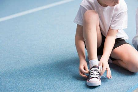 Bijgesneden foto van een jonge jongen die zijn sportschoenen op de baan vastbindt