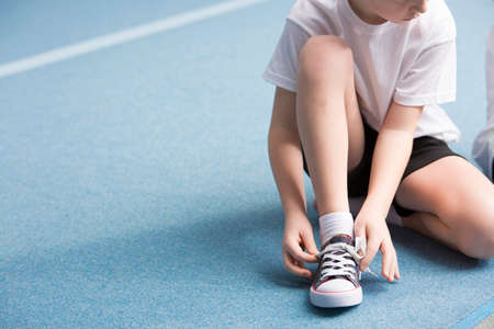 Cropped photo of a young boy tying his sports shoes on the court