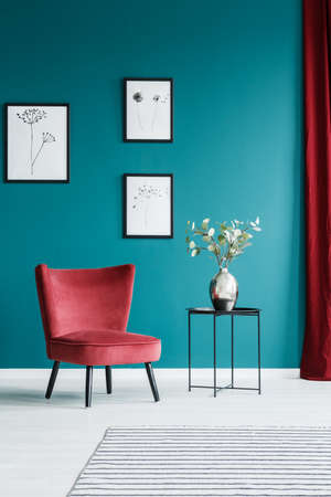 Paintings on the green wall in living room interior with red armchair and black side table with a flower vase on top