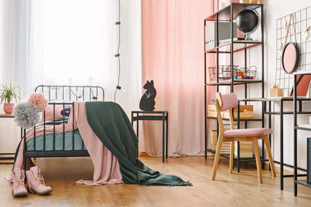Industrial black furniture and cute pink textiles in a teenage student's modern bedroom interior with cozy metal frame bed and workspace