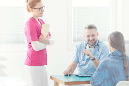 Doctors assistant in pink uniform next to a general practitioner during medical interview Stock Photo