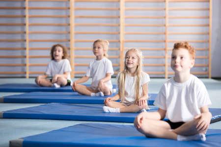 Focused pupils sitting cross-legged on blue mats during gymnastics class
