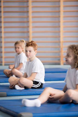Side view of pupils in sportswear during training at the school gym