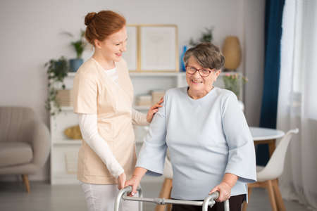 Professional medical caretaker in uniform helping smiling senior woman with a walker in a living room of private luxury healthcare clinic Stockfoto