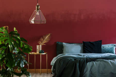Lamp above gold table next to emerald green bed in bedroom interior with plant and red wall 写真素材