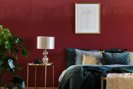 Gold lamp on table next to bed with green bedding in sophisticated red bedroom interior with poster
