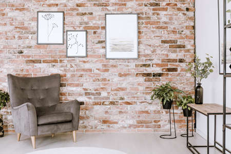 Living room interior with grey armchair, plants and posters on a red brick wall