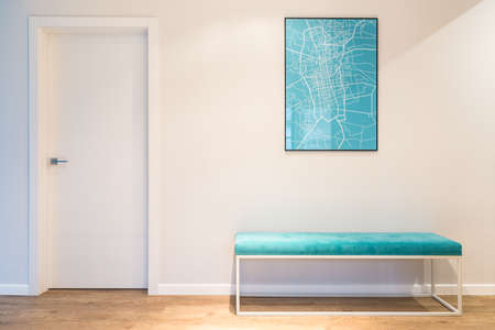 Turquoise, upholstered bench seat and a city map poster in a white house interior with wooden panels Archivio Fotografico