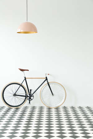 Black bike against white wall in simple interior with checkerboard floor and pink lamp