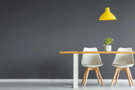 Witte stoelen aan houten tafel met plant onder gele lamp in donkergrijs eetkamer interieur met kopie ruimte