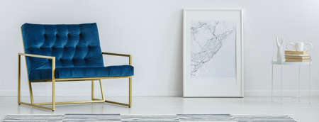 Royal blue armchair with gold frame standing in white room interior with map poster on the floor and small table with books 스톡 콘텐츠