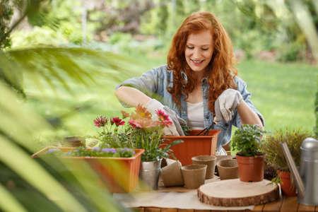 Feliz mujer pelirroja vertiendo tierra en un recipiente para flores