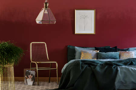 Lamp above gold chair next to green bed against red wall with poster in bedroom interior with plant