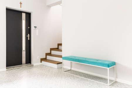 Puerta delantera negra, escaleras y un asiento de banco tapizado de color turquesa en un interior de hall de entrada blanco Foto de archivo