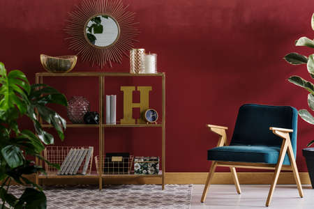 Navy blue wooden armchair next to shelves against red wall with mirror in elegant living room interior 免版税图像