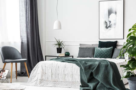 Emerald green blanket and pillows on white bed in cozy bedroom interior with gray chair and poster Imagens