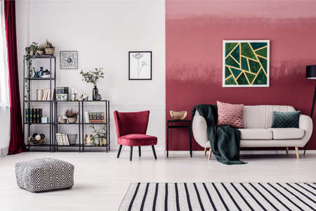 Striped carpet and pouf in spacious living room interior with red armchair and green painting