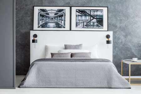 Posters above bed with grey blanket in simple hotel room interior with concrete wall 写真素材