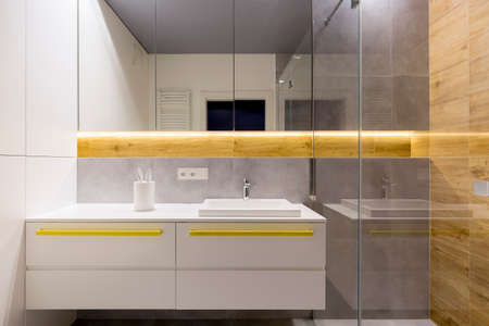 White and gray bathroom interior with yellow accents on the cupboards, steel faucet and ceramic washbasin