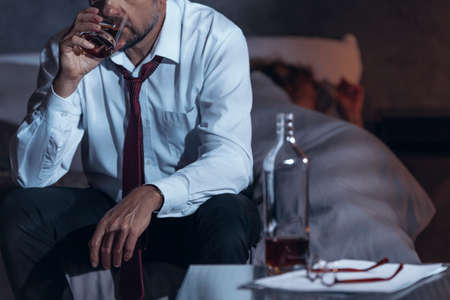 Man drinking whiskey in a suit while his woman is asleep