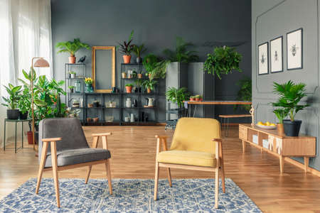 Botanic living room interior with dark walls and wooden furniture such as armchairs, table, bench and cupboard Stock Photo