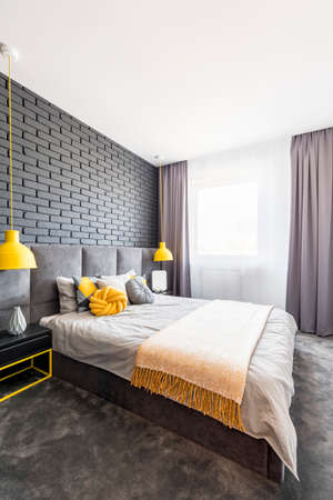 Modern, gray and yellow bedroom interior with comfy bed standing against black, brick wall between yellow lamps Stockfoto