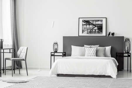 Grey chair at table near white bed in spacious contrast bedroom interior with black and white poster