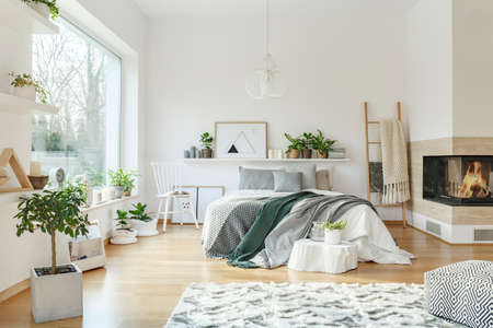 Cozy, light bedroom interior with a king-size bed, fireplace, window, rug, chair and ladder Stock Photo