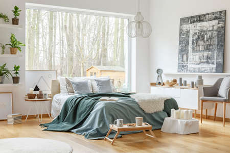 Painting above white cupboard near bed with green and pastel bedding in warm bedroom interior Foto de archivo - 101342805