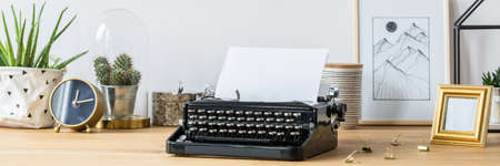 Vintage typewriter standing on a wooden home office desk with fresh plants, handmade poster and decorations Reklamní fotografie