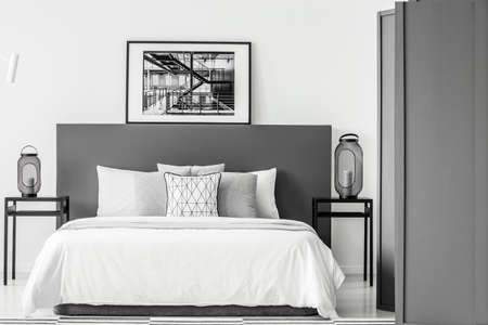 Black and white poster on bedhead of bed in bedroom interior with lanterns on tables