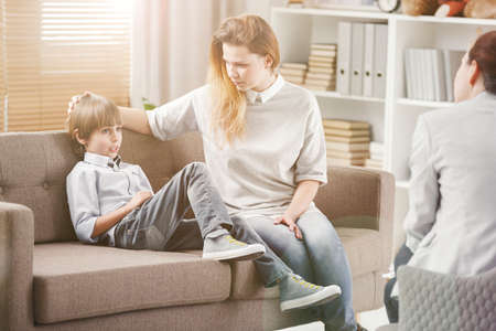 Shy kid and caring mother during consultation with psychotherapist Stock Photo