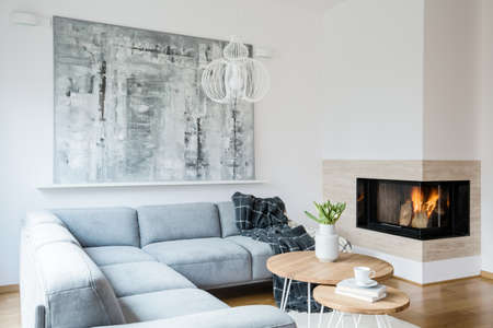 Black blanket thrown on a grey corner lounge in white living room interior with fireplace, fresh tulips in vase and big modern painting hanging on the wall Stock Photo
