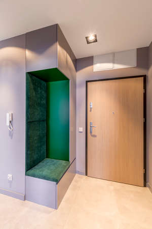Simple, spacious entrance hallway to a bright apartment interior with wooden door and a green, velvet seat