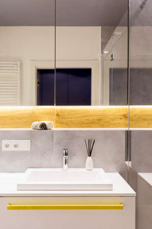 Door reflection in the mirror above white washbasin with stainless steel faucet in bright bathroom interior