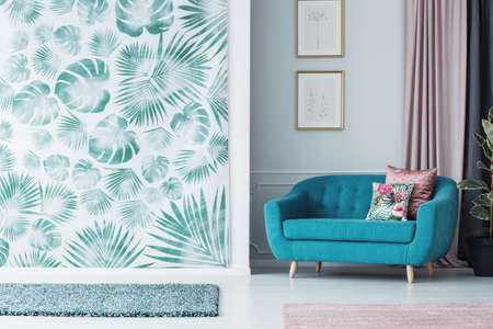 Turquoise sofa in leafy living room interior with green wallpaper and pink cloth next to posters 스톡 콘텐츠