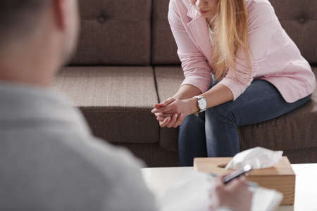 Sad woman with a problem during consultation with psychotherapist Stock Photo