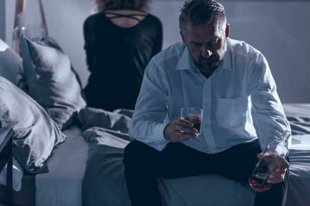 Husband sitting on the bed and holding alcohol while having a fight with his wife Stock Photo