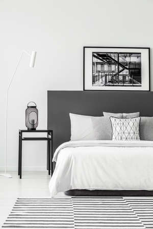 Black table next to a white bed with poster in minimal bedroom interior with carpet