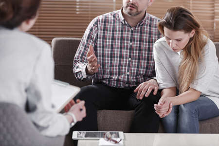 Depressed marriage talking to a mediator during therapy for couples Stock Photo
