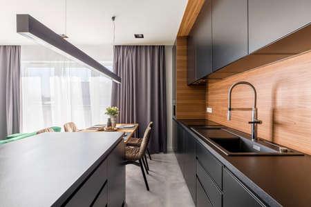 Interior de cocina con gabinetes negros, grifo de acero y mesa de madera en el comedor