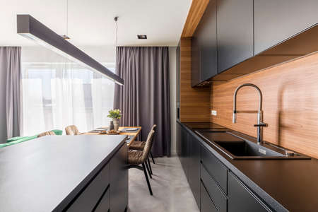 Kitchen interior with black cabinets, steel tap and wooden table in dining area