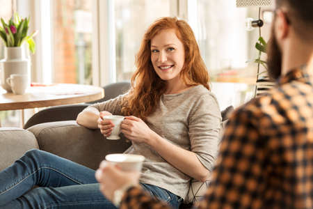 Smiling woman drinking tea and looking lovingly at her husband