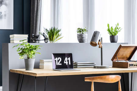Side angle of a wooden desk with a laptop showing time, plant, lamp, books and gramophone standing by the window Stock Photo - 101344173