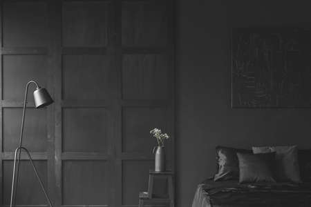 Black lamp and white flowers on wooden table in dark bedroom interior with molding on the wall