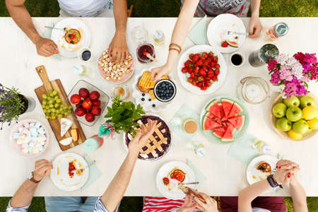 Mixed-race group of students sitting outside and sharing a meal of fruit, waffles, watermelon and apples on plates 版權商用圖片 - 101344363